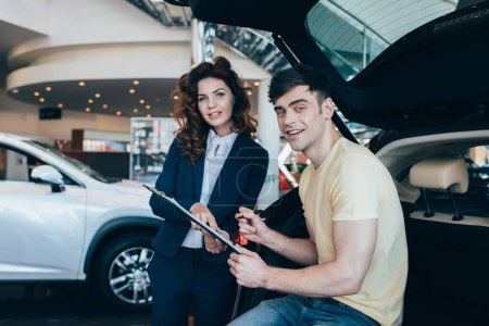 Photo for Handsome man signing paper near smiling car dealer and looking at camera - Royalty Free Image