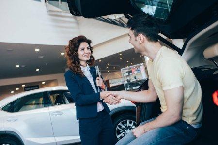 fröhlicher Autohändler und Kunde beim Händeschütteln neben Neuwagen