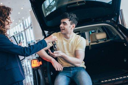 Photo pour Concessionnaire jolie voiture donnant clés de voiture à l'homme heureux assis dans une nouvelle voiture - image libre de droit