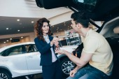 selective focus of happy customer taking car keys from attractive car dealer