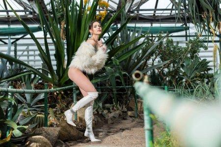 Photo pour Vue sur toute la longueur sexy femme gracieuse en fausse fourrure manteau, sous-vêtements et blanc bottes debout sur une jambe dans l'Orangerie - image libre de droit