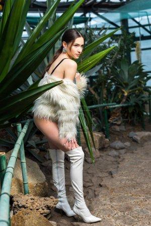 Photo pour Vue sur toute la longueur sexy femme en manteau de fourrure, des sous-vêtements et des bottes blanches dans l'Orangerie - image libre de droit