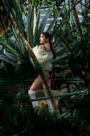 Photo pour Gracieuse fille sexy en manteau de fourrure et des bottes blanches dans l'Orangerie - image libre de droit