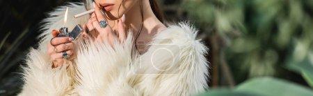 Photo pour Prise de vue panoramique de la sexy jeune femme en fausse fourrure manteau éclairage cigarette au jardin botanique - image libre de droit