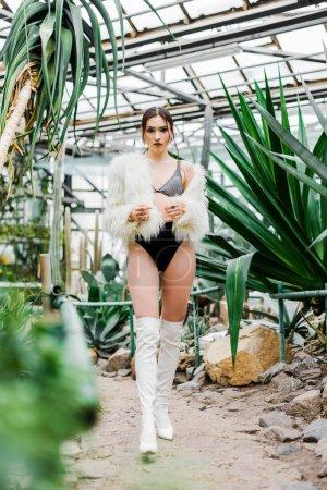 Photo pour Vue sur toute la longueur sexy femme en manteau de fourrure et des bottes à l'Orangerie - image libre de droit