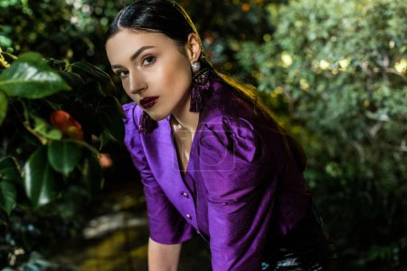 Photo for Pretty young woman in purple blouse looking at camera in botanical garden - Royalty Free Image