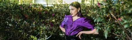 Photo for Panoramic shot of elegant young woman in purple blouse standing with arms akimbo in orangery - Royalty Free Image