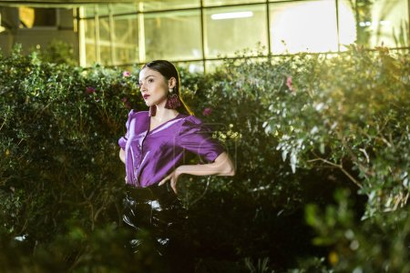 Photo for Elegant young woman in purple blouse standing with arms akimbo in orangery - Royalty Free Image