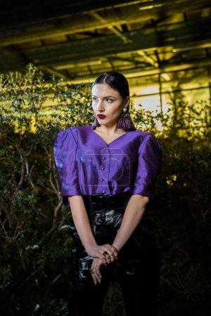 Photo pour Pensive jeune femme en chemisier violet regardant loin dans l'orangerie - image libre de droit
