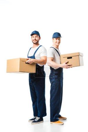 Photo pour Deux beaux déménageurs regardant la caméra tout en transportant des boîtes en carton sur blanc - image libre de droit