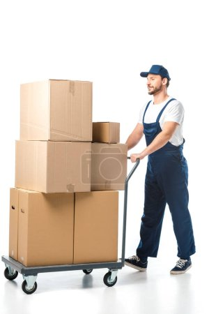 Photo for Handsome mover in uniform transporting cardboard boxes on hand truck isolated on white - Royalty Free Image