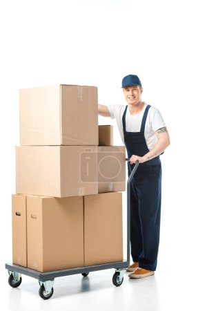 Photo for Handsome mover in uniform smiling while transporting cardboard boxes on hand truck isolated on white - Royalty Free Image
