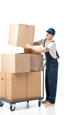 handsome mover in uniform transporting cardboard box near hand truck with packages isolated on white