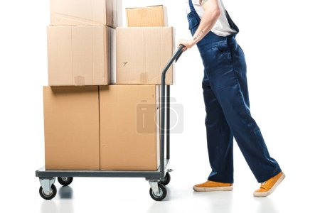 Photo for Cropped view of mover in uniform transporting cardboard boxes on hand truck on white - Royalty Free Image