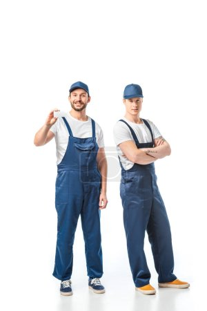 Photo for Movers in uniform looking at camera and showing card with copy space on white - Royalty Free Image
