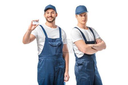 Photo pour Deux déménageurs en uniforme regardant la caméra et montrant la carte de visite vide isolé sur blanc - image libre de droit
