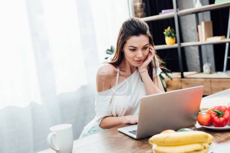 Photo for Attractive young woman using laptop at table in kitchen - Royalty Free Image