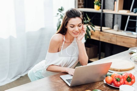 Cheerful girl using laptop on wooden table in kitchen