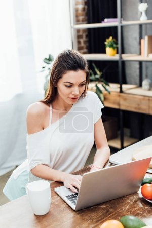fröhliches Mädchen mit Laptop auf Holztisch in Küche