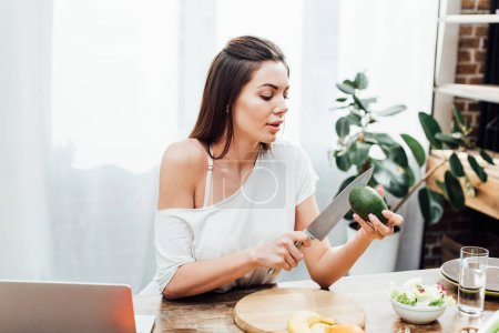 Photo for Sexy girl cutting avocado with knife at wooden table in kitchen - Royalty Free Image