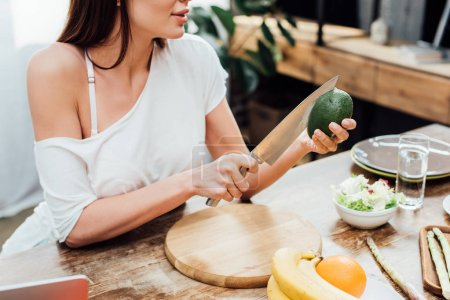 Photo for Cropped view of girl cutting avocado with knife at wooden table in kitchen - Royalty Free Image