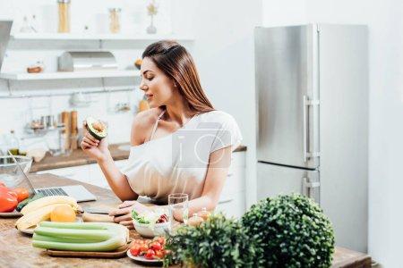 ziemlich stylisches Mädchen hält geschnittene Avocado am Tisch in der Küche