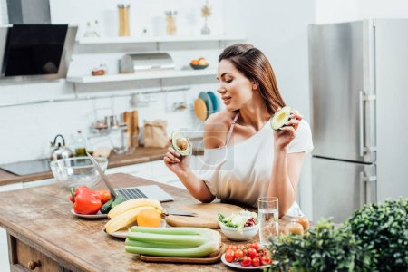 Photo for Pretty stylish girl holding cut avocado near table in kitchen - Royalty Free Image