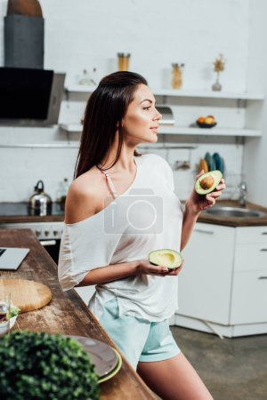 Pretty stylish girl holding cut avocado near table in kitchen
