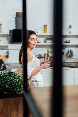 Photo for Stunning girl holding glass of water and looking at camera in kitchen - Royalty Free Image
