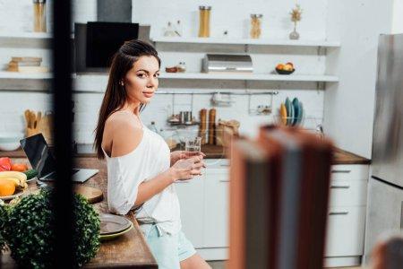 Muchacha atractiva de pie cerca de la mesa de madera y sosteniendo el vaso de agua en la cocina