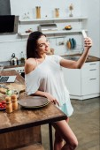 Smiling girl holding smartphone and taking selfie in kitchen