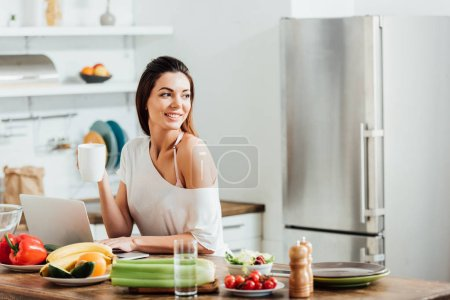 Photo for Charming girl drinking coffee while using laptop in kitchen - Royalty Free Image