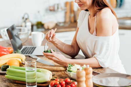 Photo for Partial view of woman eating avocado with spoon in kitchen - Royalty Free Image