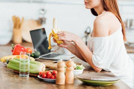 Foto de Vista parcial de la mujer joven sosteniendo plátano fresco en la cocina - Imagen libre de derechos