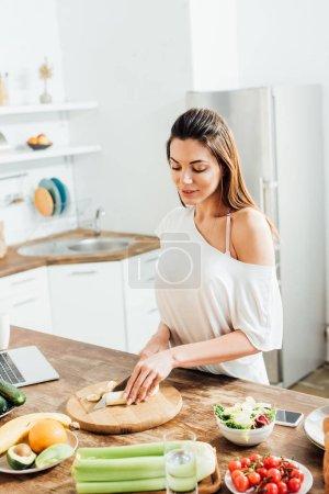Foto de Hermosa mujer joven cortando plátano con cuchillo en la cocina - Imagen libre de derechos