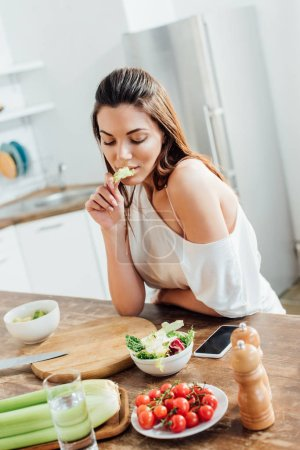 Photo for Pensive girl sitting at table and eating salad in kitchen - Royalty Free Image