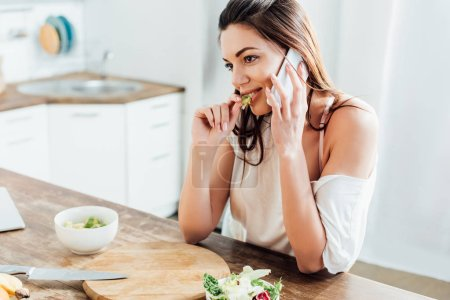 Photo for Pretty girl eating salad and talking on smartphone in kitchen - Royalty Free Image