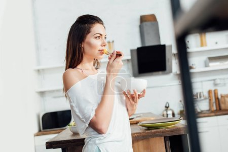 Photo for Dreamy woman holding bowl and eating cut fruit in kitchen - Royalty Free Image