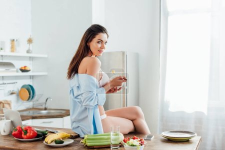 Photo for Sexy girl in underwear and shirt sitting on table and eating fruit salad - Royalty Free Image
