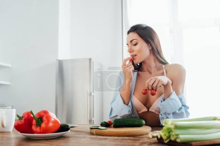 Photo for Sexy girl in bra and shirt eating cherry tomatoes in kitchen - Royalty Free Image