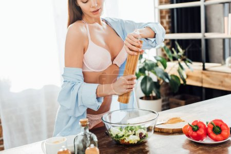 Photo for Cropped view of sexy young woman in underwear and shirt seasoning vegetable salad - Royalty Free Image