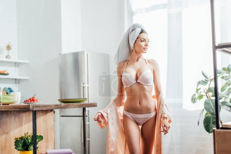 Photo for Sexy woman in white lingerie and housecoat with towel on head in kitchen - Royalty Free Image