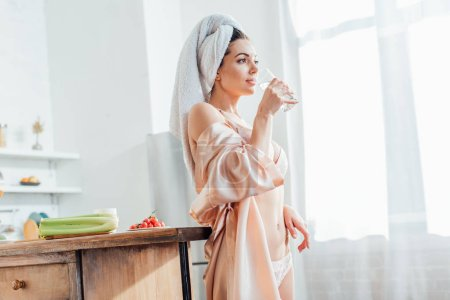 Photo for Sexy girl in white lingerie and housecoat holding glass of water in kitchen - Royalty Free Image