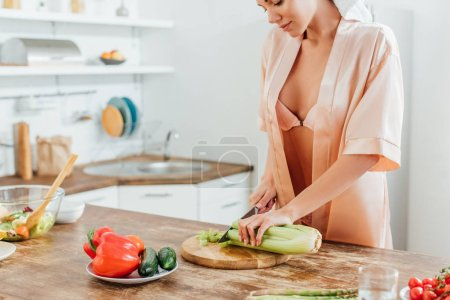 Photo for Cropped view of sexy woman in housecoat with towel on head cutting celery with knife in kitchen - Royalty Free Image