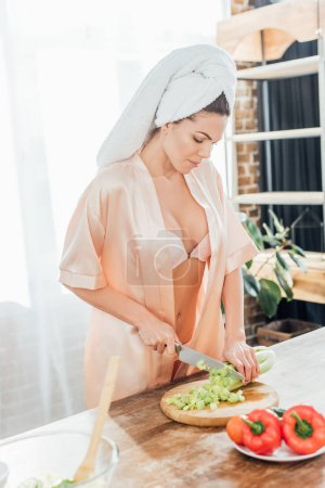 Photo for Sexy woman in housecoat with towel on head cutting celery with knife in kitchen - Royalty Free Image