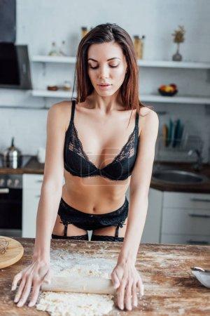 Photo pour Femme sexy en lingerie noire déroulant la pâte avec rouleau à pâtisserie - image libre de droit
