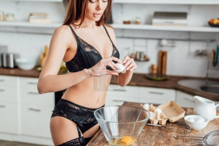 Photo for Partial view of sexy woman in black lingerie breaking egg in glass bowl - Royalty Free Image