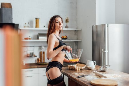 Photo for Sexy woman in black lingerie whipping eggs with whisk in kitchen - Royalty Free Image