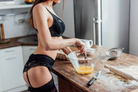 Photo for Cropped view of sexy woman in black lingerie whipping eggs with whisk in kitchen - Royalty Free Image