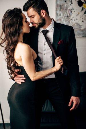 Photo pour Jolie femme en robe noire portefeuille cravate d'homme passionné, debout en costume - image libre de droit